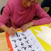 une élève en calligraphie écrit sur une feuille